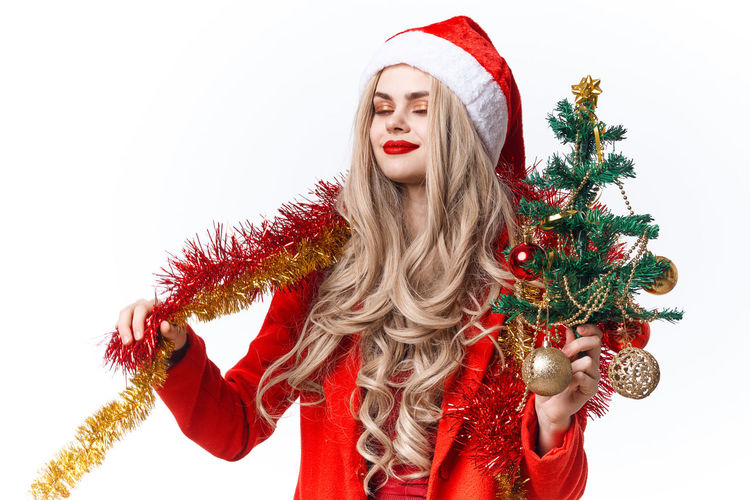 Portrait of young woman with christmas tree against white background