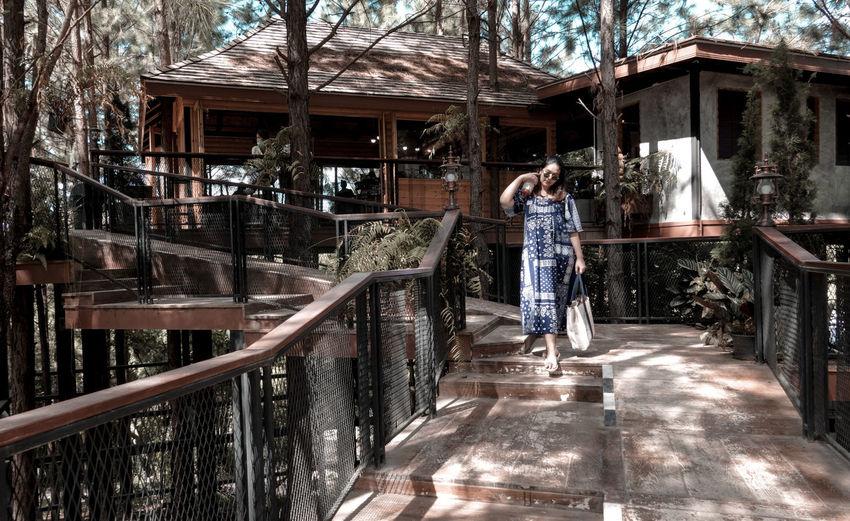 Woman on railing against trees