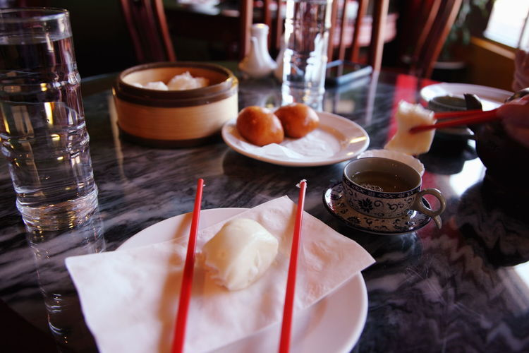 Close-up of fresh chinese dumplings with tea served on table in restaurant