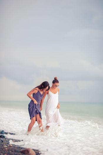 Rear view of friends enjoying on beach against sky