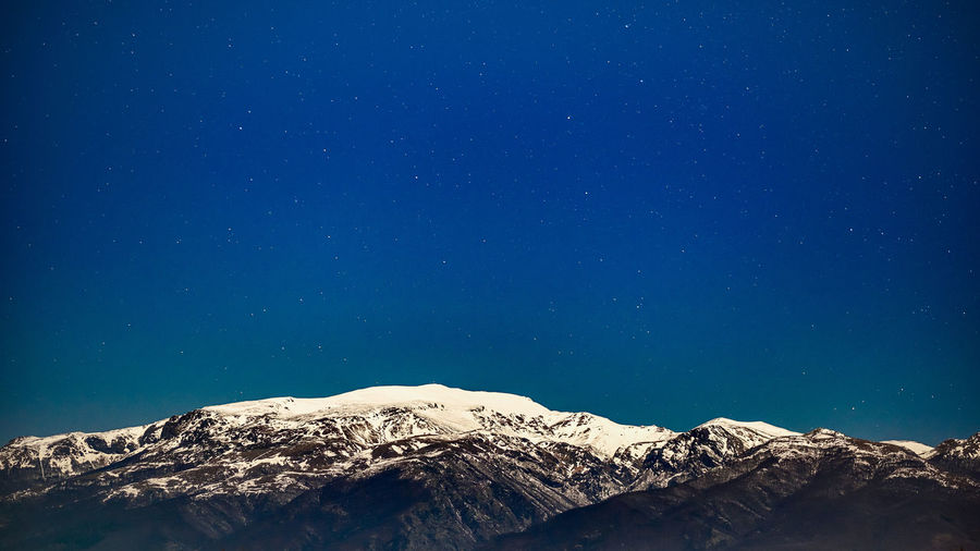 Moonlit snowcapped peak and clear stars-filled sky - color version with more details on the mountains. Mountain Sky Beauty In Nature Scenics - Nature Star - Space Astronomy Blue Tranquility Night No People Space Tranquil Scene Cold Temperature Snow Mountain Range Low Angle View Nature Snowcapped Mountain Winter Idyllic Mountain Peak Copy Space Long Exposure