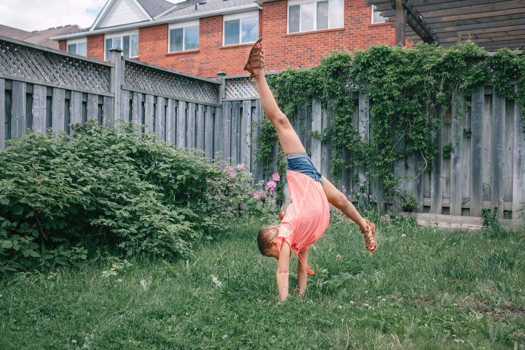 Full length of girl doing handstand in yard