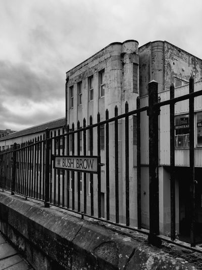 City Street Architecture Black And White Building Exterior Built Structure Cloud - Sky Day Fence History monochrome photography No People Outdoors Railings Sky Street Sign Urban Decay