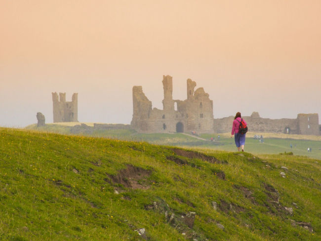 Dunstanburg Casle Castle Dunstanburgh Castle English Castles Ancient Architecture Beauty In Nature Day Fog Grass History Lifestyles Nature One Woman Only Outdoors People Real People Scenics Sky Standing Sunset Walking Women
