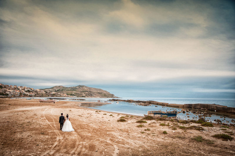 Rear View Of Wedding Couple Walking At Beach During Sunset