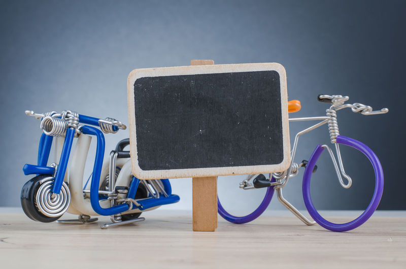 miniature handcrafted scooter and bicycle on wooden desk shot over lighting effect Still Life No People Indoors  Technology Blue Communication Medical Equipment Stationary Close-up Mode Of Transportation Metal Land Vehicle Table Flooring Transportation Connection Wireless Technology Copy Space Blank