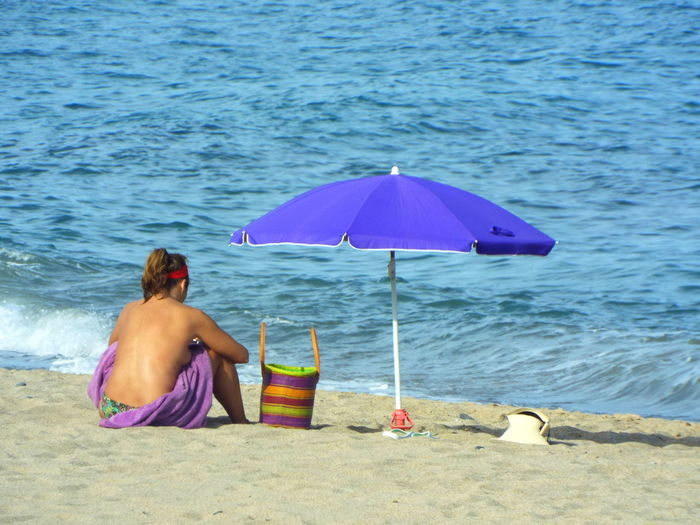 Rear view of seductive woman sitting at beach on sunny day