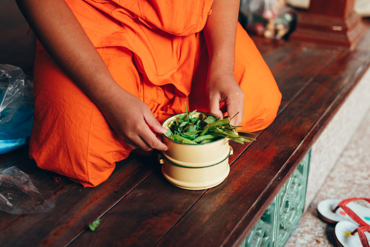 Midsection Men Orange Color Monk  Monks Robe Cloth Fabric Detail Preparation  Preparing Food Floor Herbs Greens