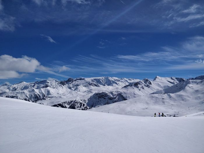 Scenic view of snowcapped landscape by mountains against blue sky