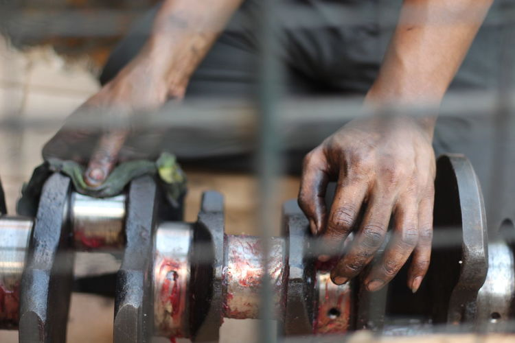 Midsection Of Greasy Mechanic Hands On Machinery At Workshop
