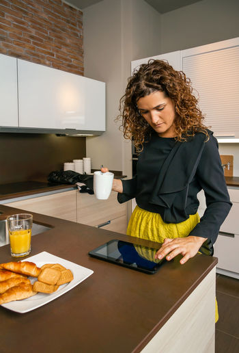 Woman Using Digital Tablet While Having Breakfast In Kitchen