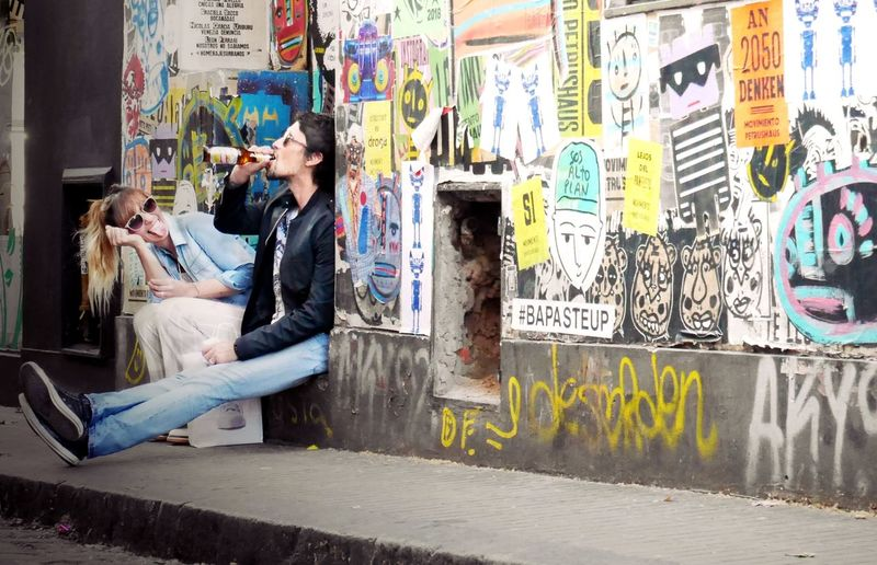 Adult Architecture Art And Craft Casual Clothing City Communication Creativity Day Full Length Graffiti Hairstyle Leisure Activity Looking One Person Outdoors Real People Side View Sitting Wall - Building Feature Women Young Adult