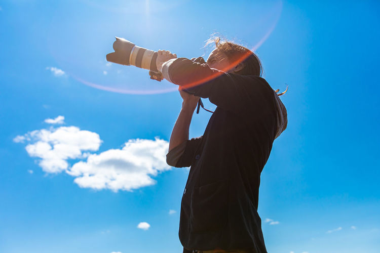 Low angle view of woman photographing against sky