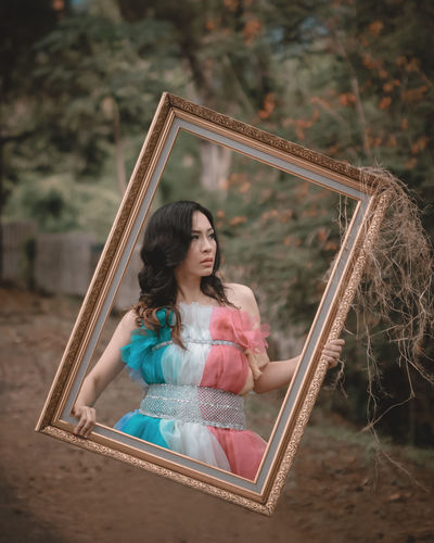 Digital composite image of woman looking away while holding picture frame
