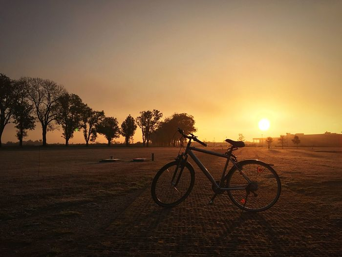 Bicycle On Field Against Sunset Sky