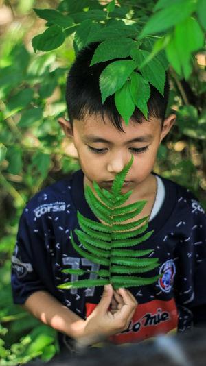 Cute thoughtful boy against plants