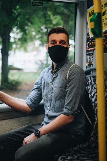 Portrait of mid adult man wearing mask sitting in bus