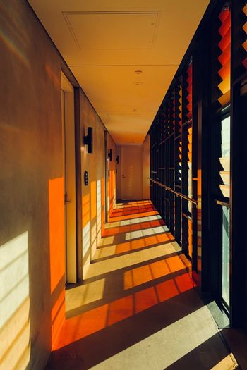 Architecture Sunlight Arcade Corridor Built Structure Shadow Creative Space Building The Way Forward No People Direction Indoors  Entrance Day Door Orange Color Wall - Building Feature Flooring Diminishing Perspective Architectural Column