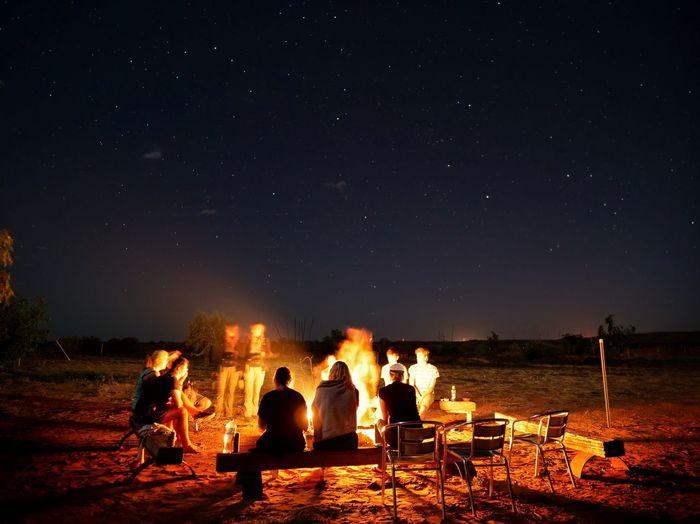 People enjoying bonfire against sky at night