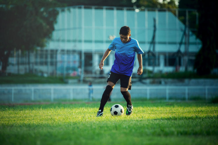 Rear view of man playing soccer ball on field