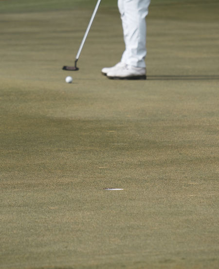 Low section of person standing on golf ball