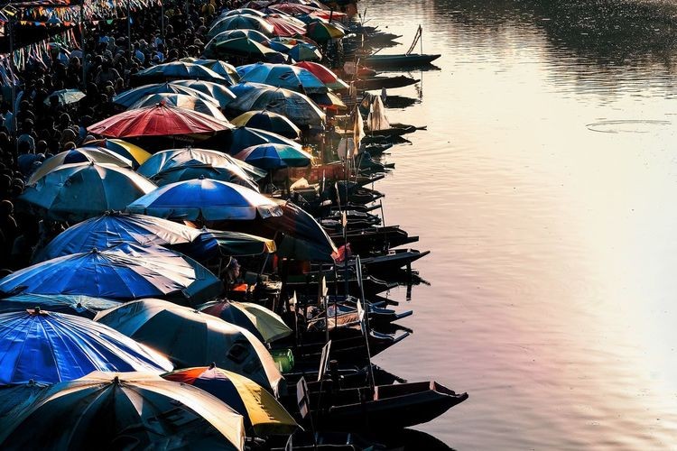 Boats with umbrellas by river
