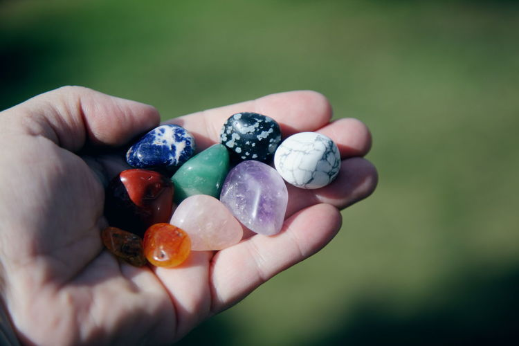 Cropped hand of person holding colorful stones