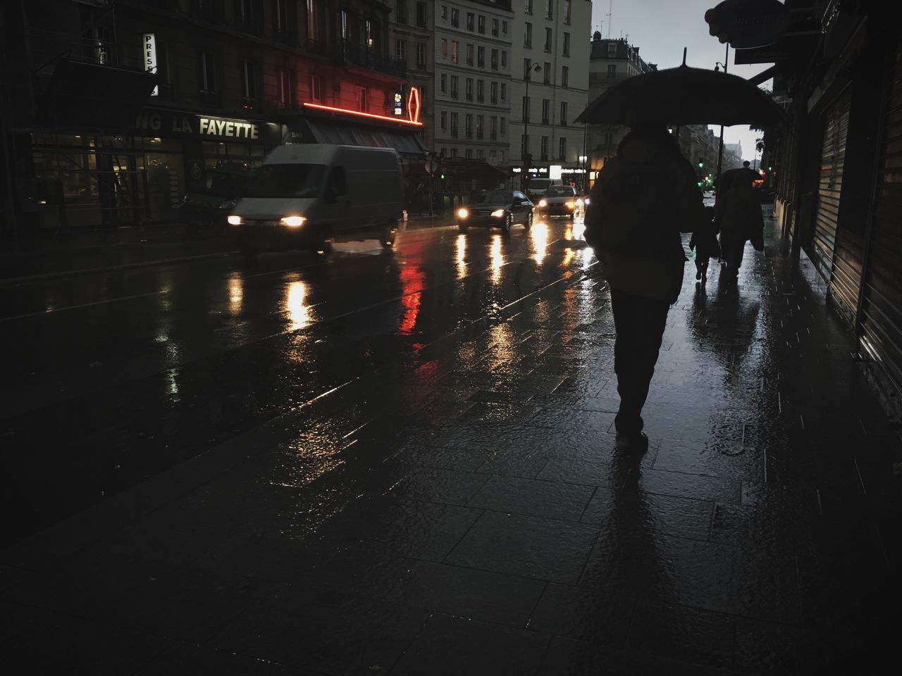 rain, wet, rainy season, weather, street, architecture, walking, built structure, city, land vehicle, real people, city life, building exterior, road, protection, outdoors, men, raindrop, water, lifestyles, night, two people, women, under, full length, people