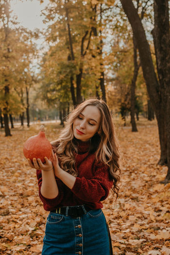 Portrait of smiling young woman holding autumn leaves