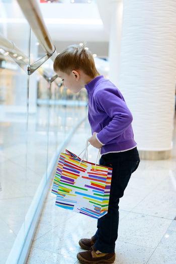 Full length of boy holding shopping bag standing at shopping mall
