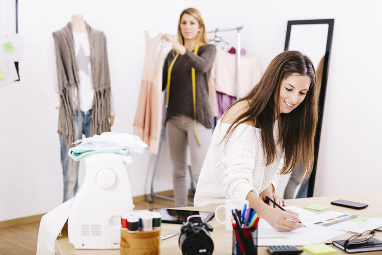 Two young designers working in their small business. At Home Desk Entrepreneur Fashion Happy Small Business Working Beautiful Woman Clothes Comercial Design Designing Fashion Fashion Designer Indoors  Professional Smiling Standing Tools Two People Women Young Adult Young Women