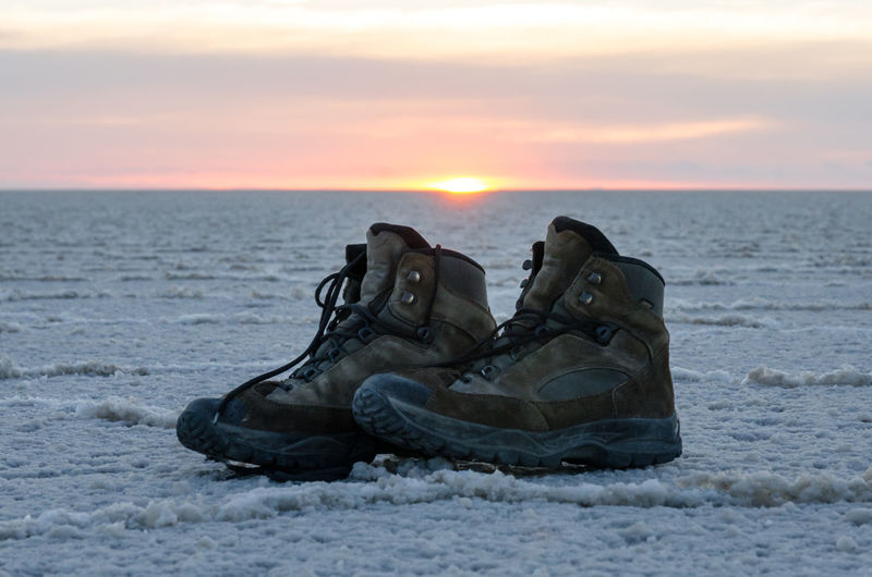 Abandoned shoes by sea against sky during sunset