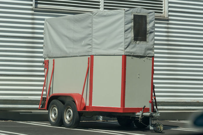 Old horse transport trailer in front of a metal wall. Animal Transport Cargo Container Corrugated Iron Day Horse Carts Horse Trailer Horse Transportation Land Vehicle Metal Mode Of Transport No People Outdoors Red Transportation