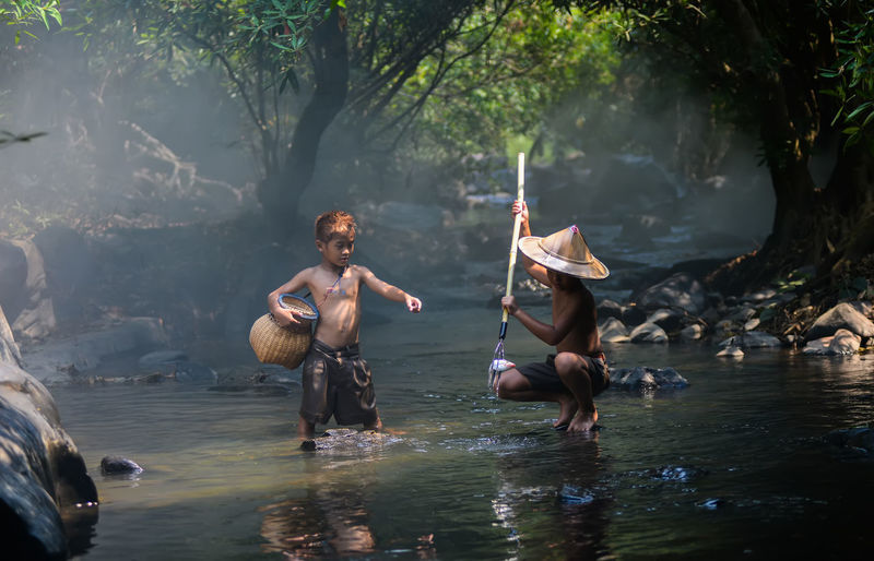 Shirtless brothers fishing in river at forest