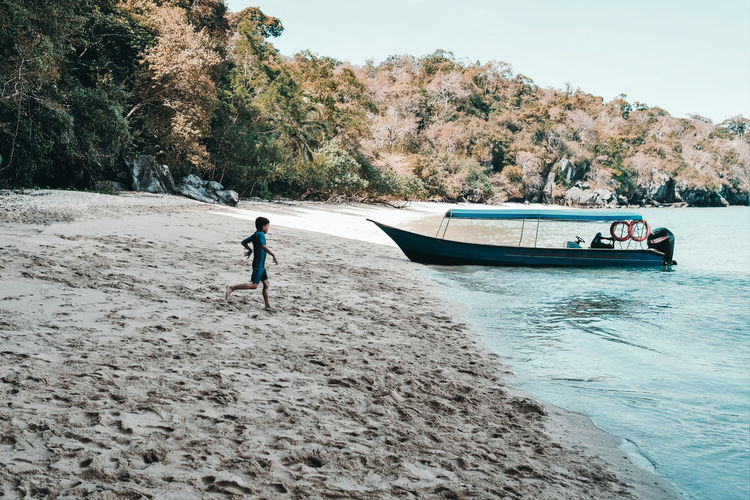 Vacations Alone On The Beach Beach Boat Boy Running Langkawi Island Malaysia Leisure Activity Lifestyles Nature Nautical Vessel One Person Outdoors Paradise Beach Sandy Beach Sea