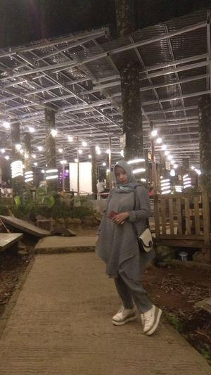 Full length of man standing in illuminated city at night