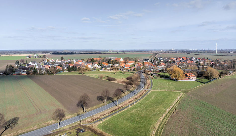 Aerial view of a village near Wolfsburg. With the main road in the foreground and a farm with a pond at the edge of the village. Made with drone Farm Field Roof Rooftop Agriculture Architecture Beauty In Nature Building Exterior Built Structure Day Drone Landscape Field Landscape Meadow Nature No People Outdoors Patchwork Landscape Photo From Above Rural Scene Scenics Sky Suburb Tree Village