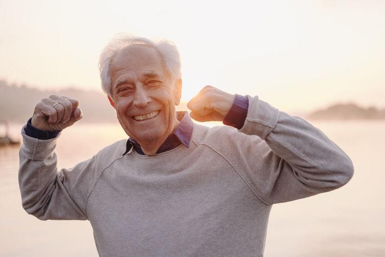 Portrait of smiling man holding camera against sky