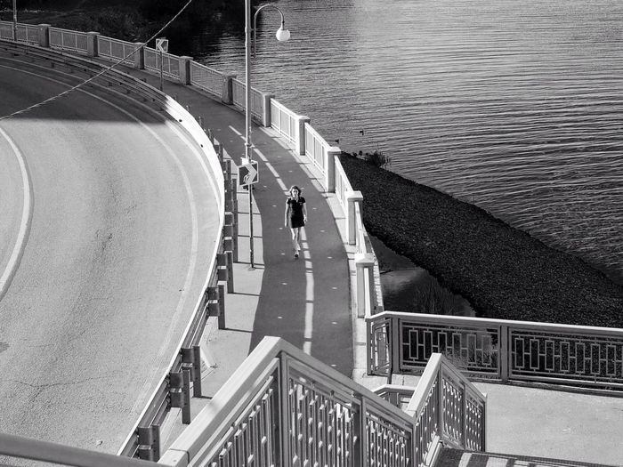 High angle view of woman walking on sidewalk by road over lake