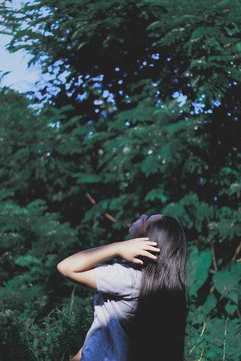 Rear View Of Young Woman Standing Against Trees