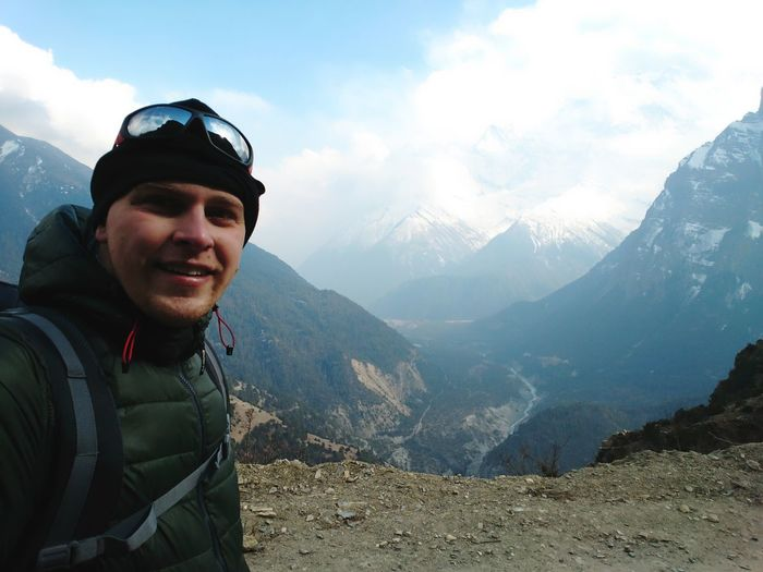 Portrait Of Smiling Man Standing On Mountains
