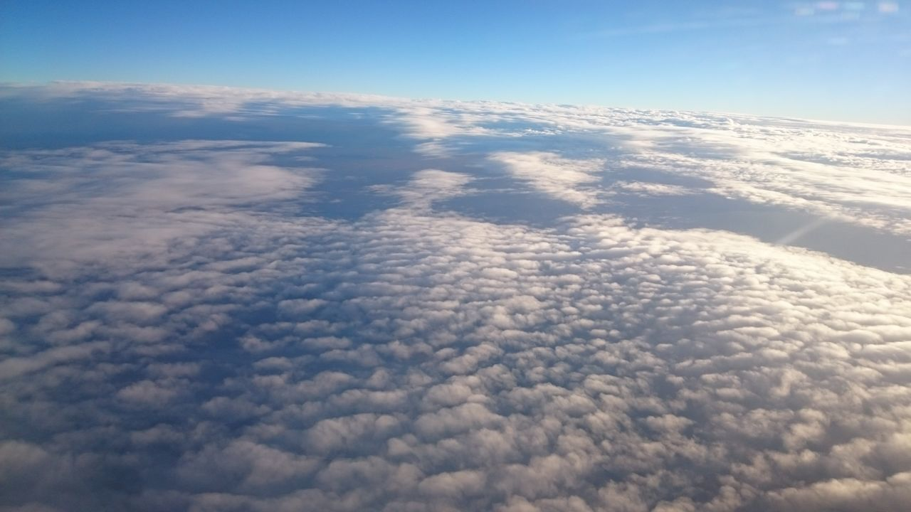 nature, beauty in nature, sky, aerial view, cloud - sky, no people, cloudscape, scenics, white color, blue, tranquility, outdoors, day, sky only, sunlight, the natural world, backgrounds, airplane, flying