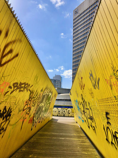 Graffiti on yellow wall by building against sky