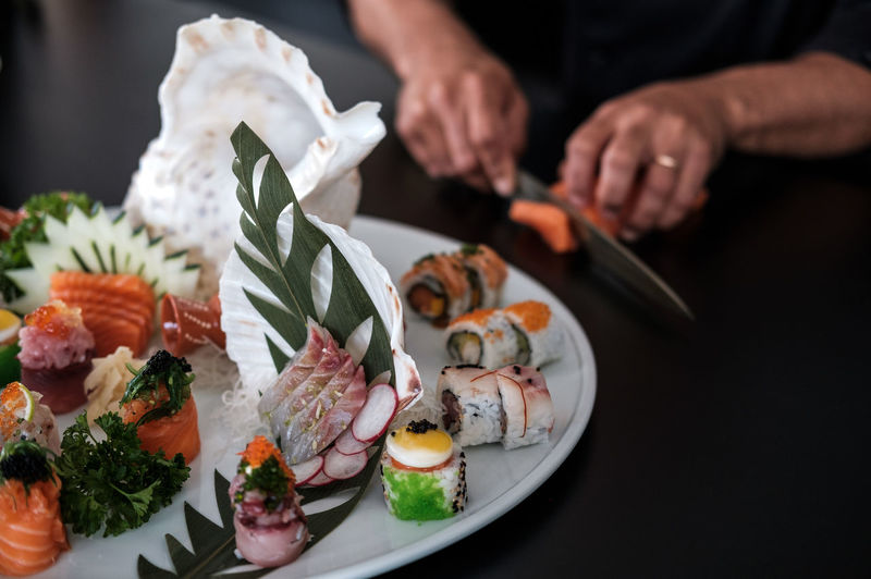 Close-up of sushi served in plate while cropped hands cutting food in background