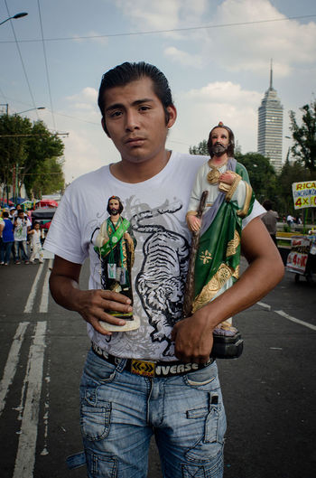 A devotee to San Judas arrives to a church in Mexico City where many followers come on the 28th of each month. Casual Clothing Devotee Devotion Lifestyles Outdoors Person Portrait Religion San Judas  Sky Statue Street Streetportrait The Street Photographer - 2016 EyeEm Awards