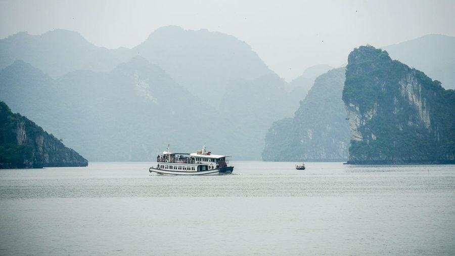 Sailboats sailing on sea against mountains
