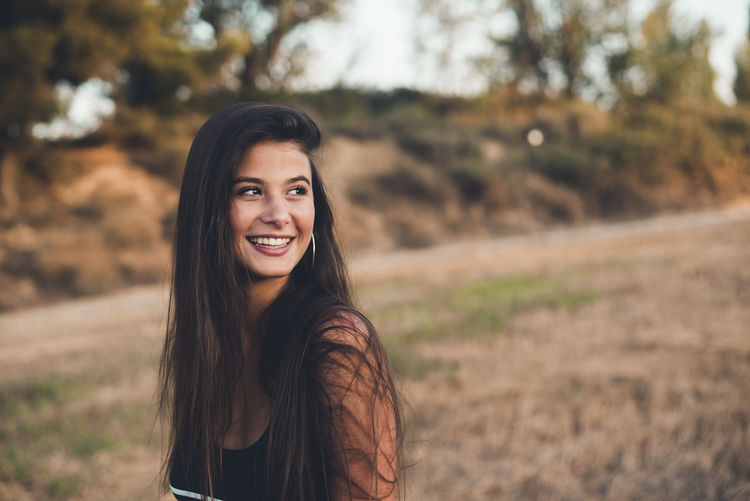 Portrait of smiling young woman standing on land