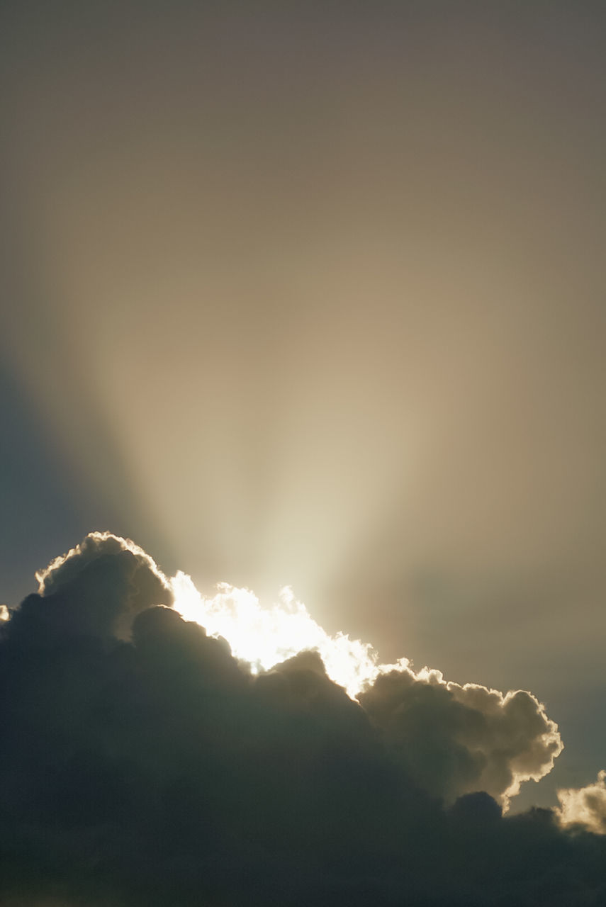 LOW ANGLE VIEW OF SUNLIGHT STREAMING THROUGH CLOUDS AGAINST SKY