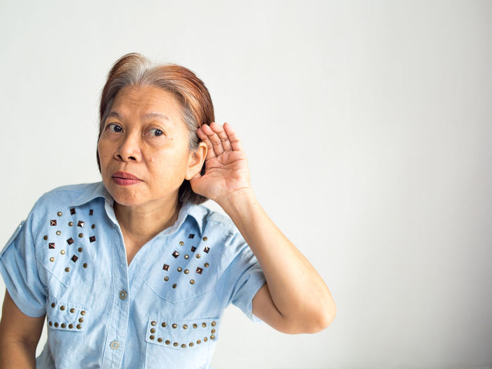Woman listening against white background