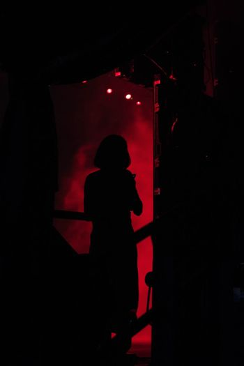 Silhouette woman standing against illuminated lights at night